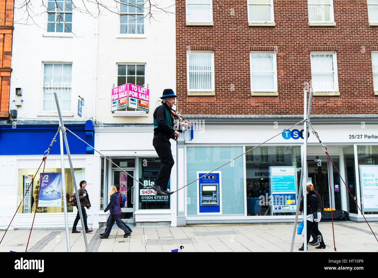 Street performer playing violin on one leg on tightrope York city centre UK - Stock Image