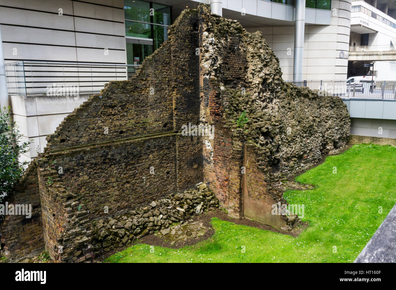 Surviving part of old London Wall exposed on one of few remaining WWII bomb sites in Noble St. Shows stonework from - Stock Image