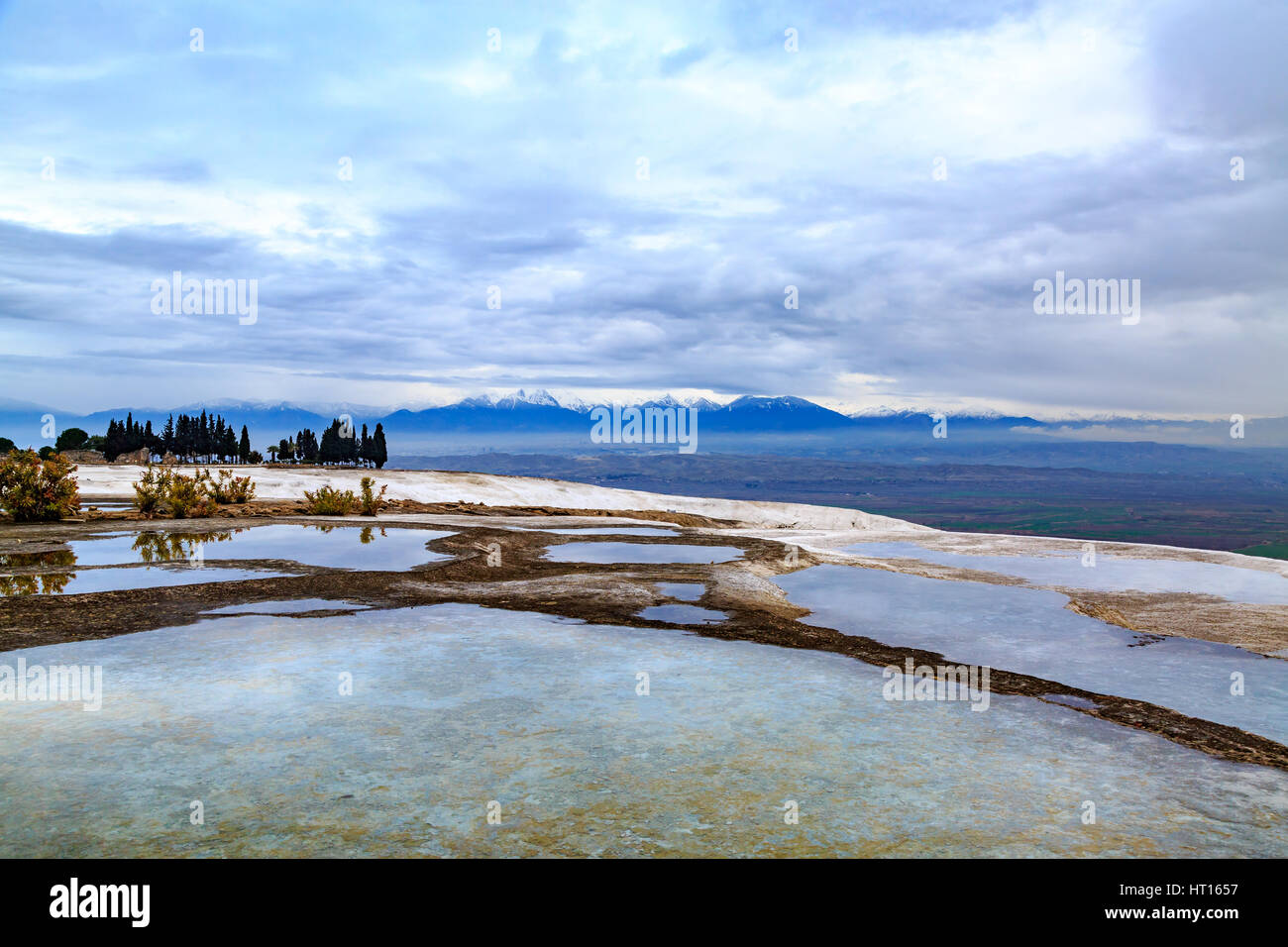 Colorful pamukkale travertines with mountains background - Stock Image