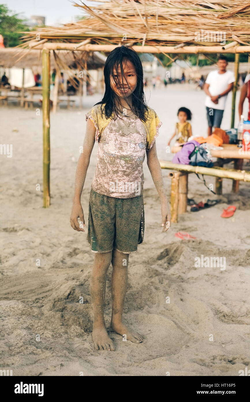 Young little girl dirty from sand on the beach - Stock Image