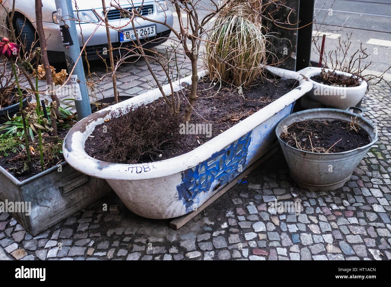 Berlin, Prenzlauer Berg. Unusual plant containers on urban pavement, bath,tin tub and toilet Stock Photo