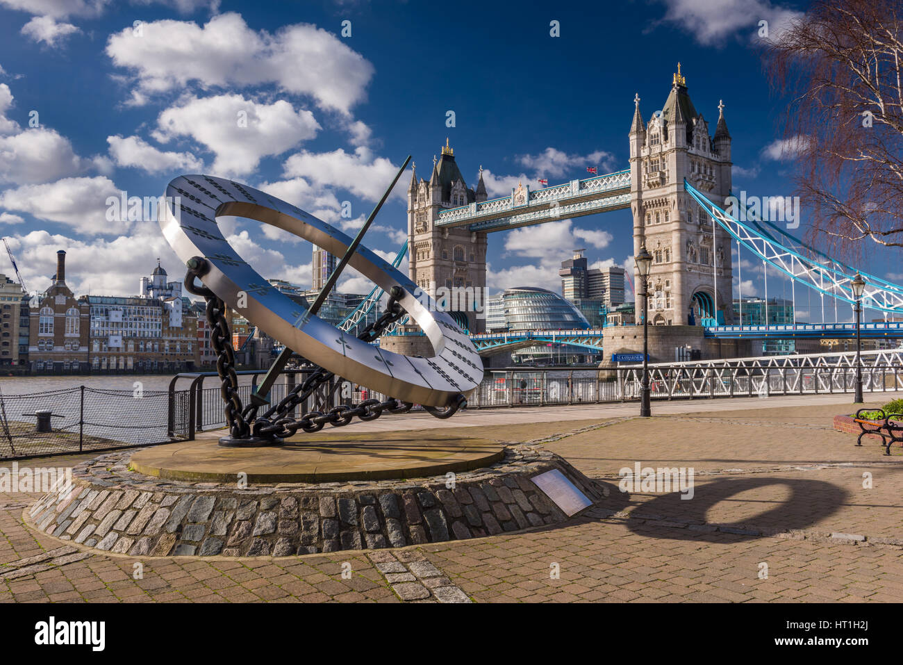 The Tower Hotel Sundial, designed by Wendy Taylor, with Tower Bridge in the background on a cold but bright day - Stock Image