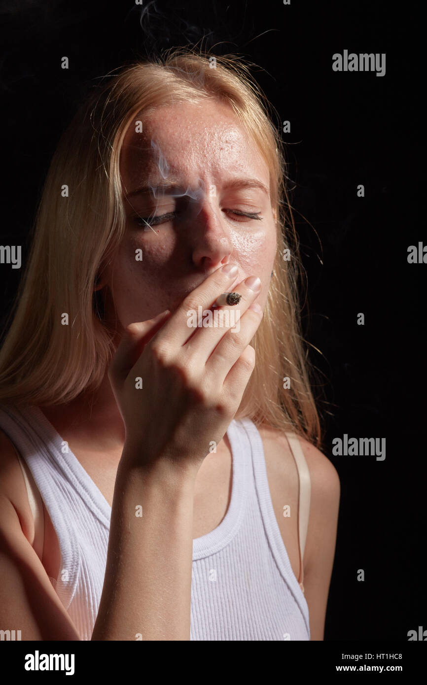 girl with pimple skin smoking joint with marijuana - Stock Image