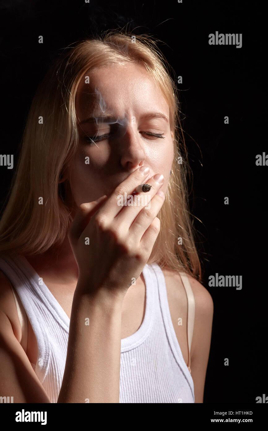 sad blond girl smoking joint with marijuana - Stock Image