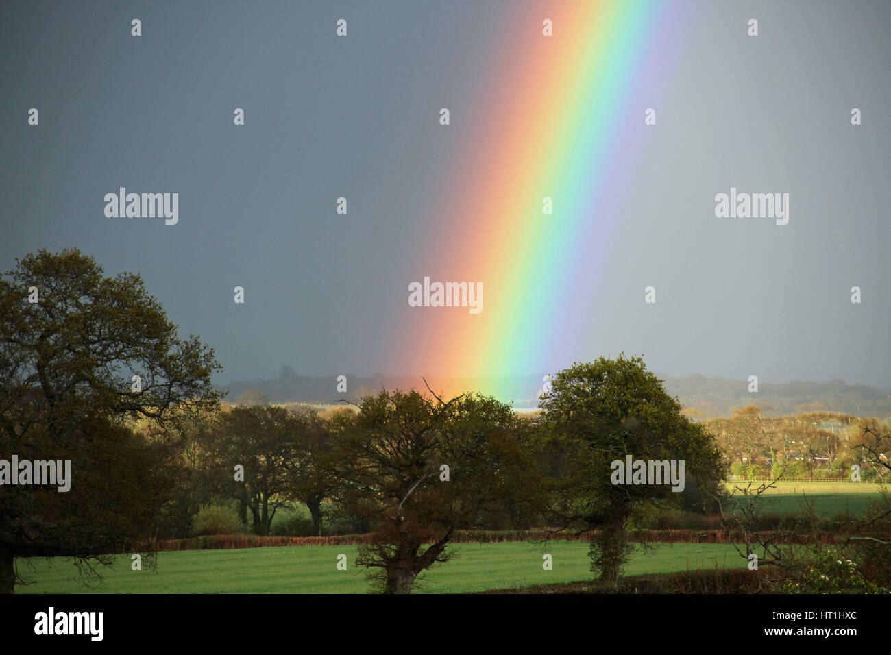 Vibrant colourful rain bow over the English country side - Stock Image