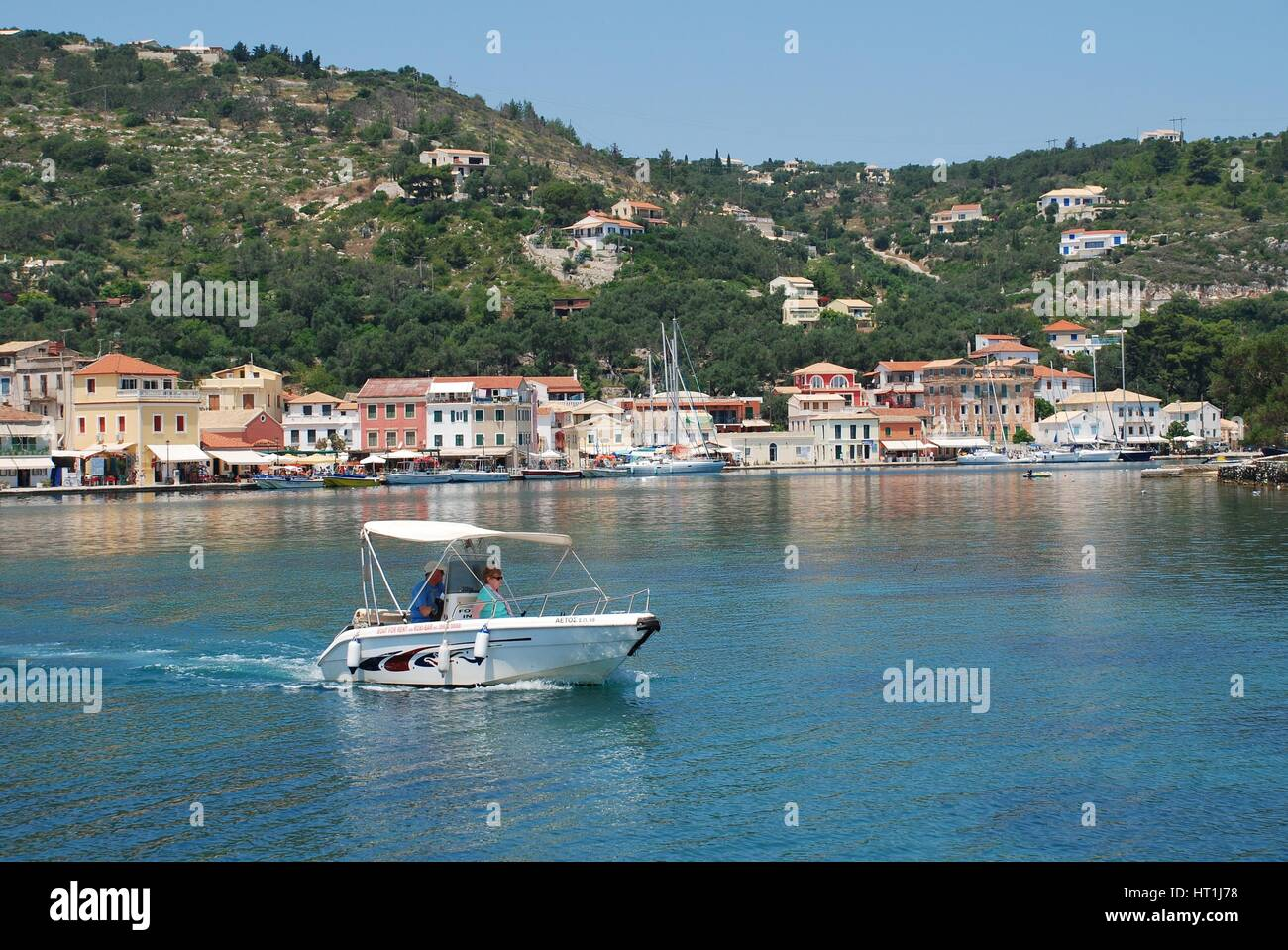 A small boat head out of Gaios harbour on the Greek island of Paxos. - Stock Image