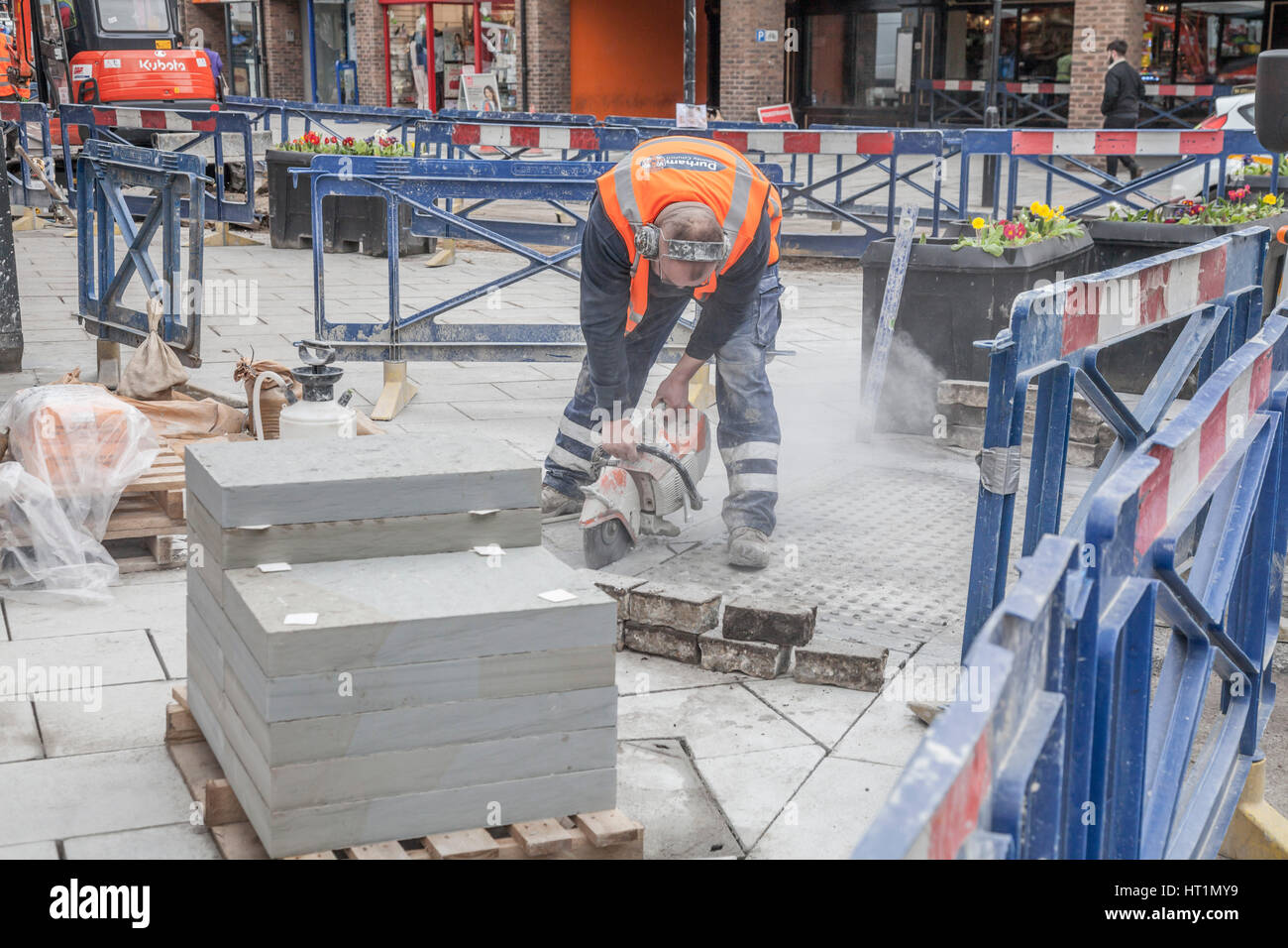A council workman using a power tool to cut block paving in Durham city,England,UK - Stock Image