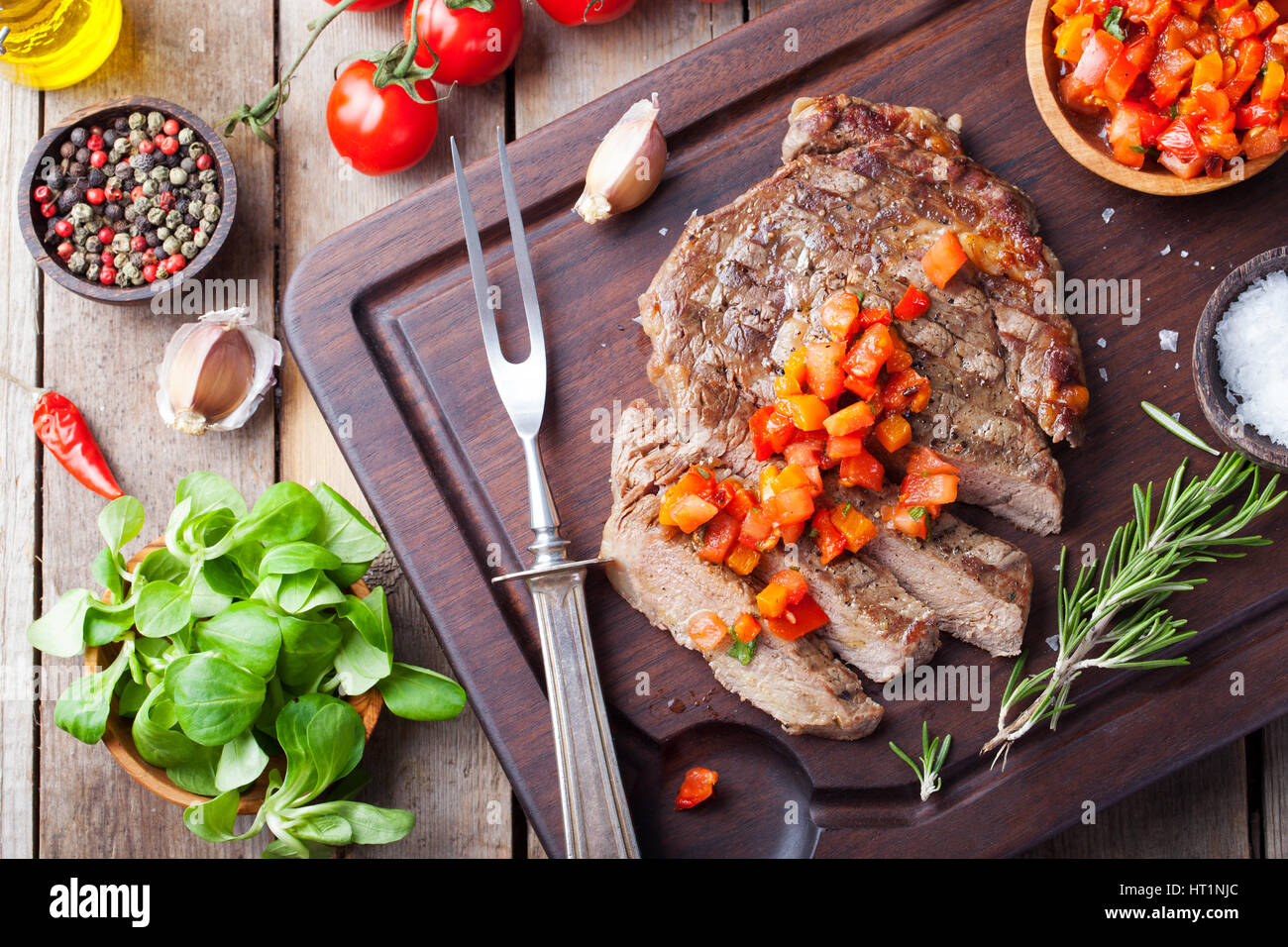 Beef steak well done with tomato and pepper salsa on a wooden background - Stock Image