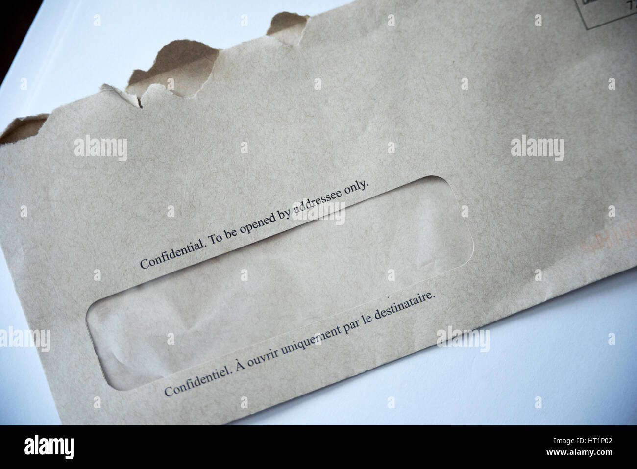 A grey envelope with 'Confidential To Be Opened By Addressee only' written in English and French on the - Stock Image