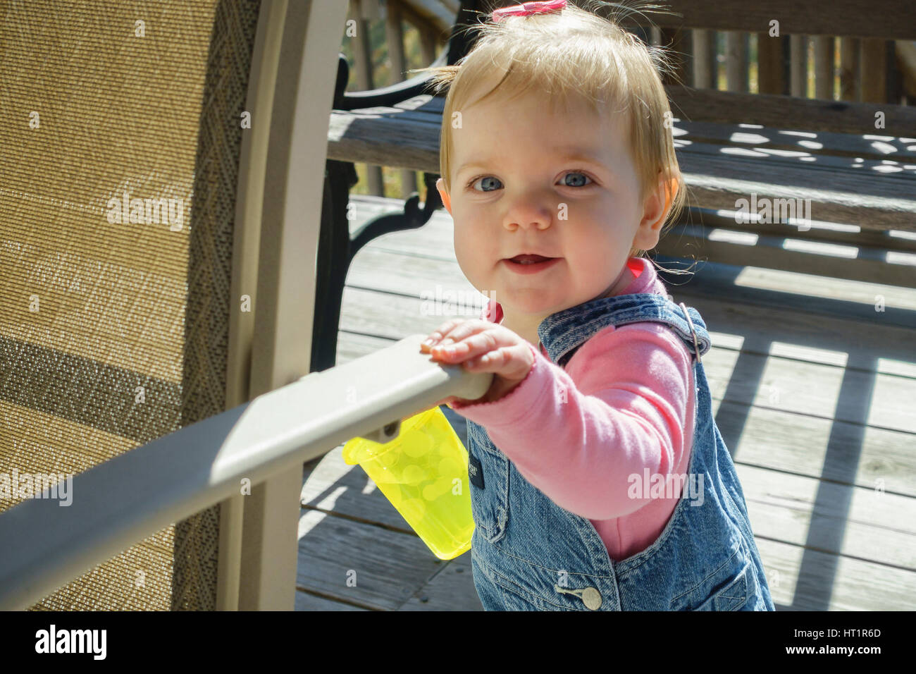 One year old smiling Caucasian baby girl in overalls with a drink cup, standing on an outdoor deck with sunshine. - Stock Image