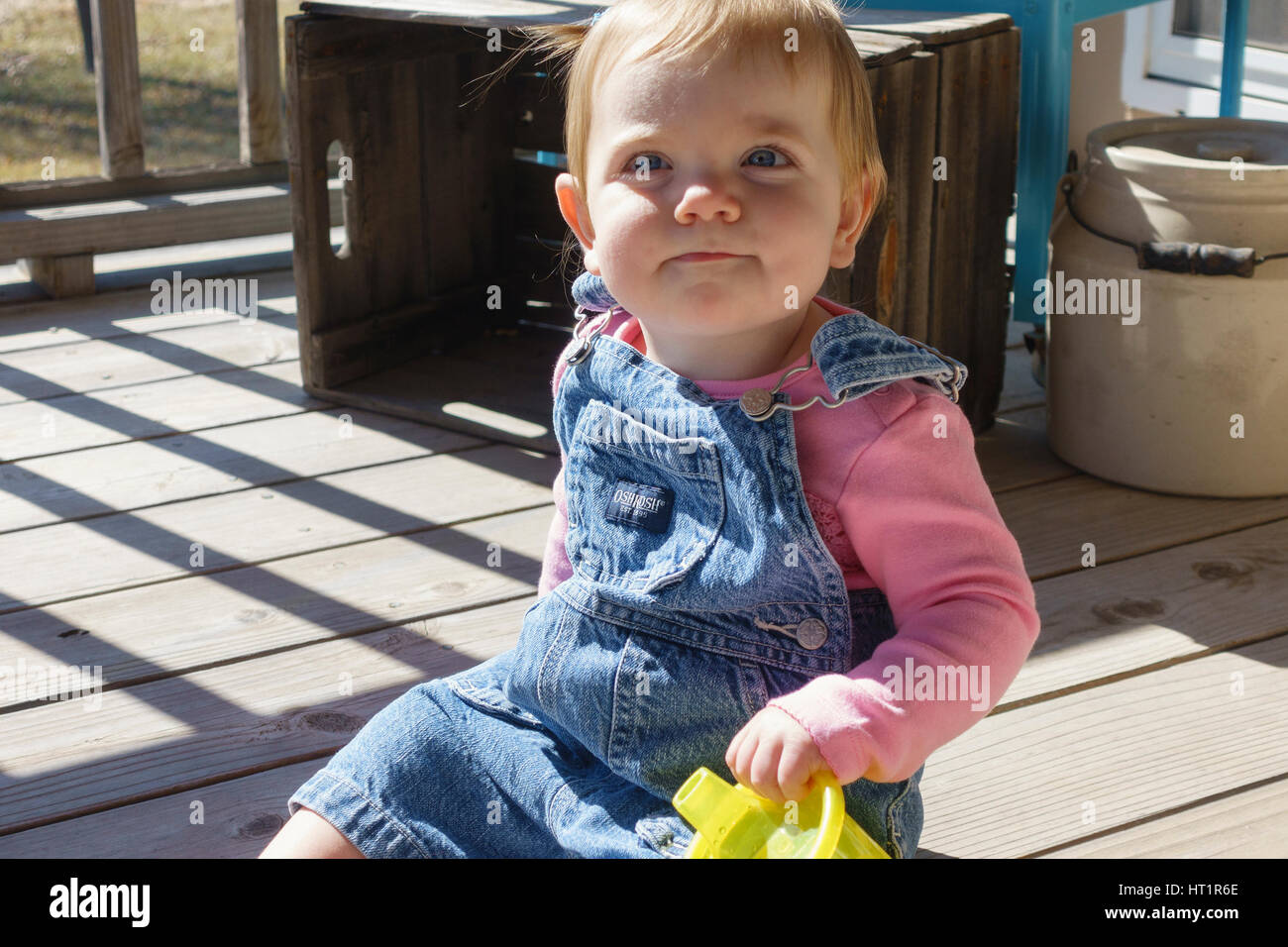One year old smiling Caucasian baby girl in overalls sitting on an outdoor deck with a drink cup. Kansas, USA. - Stock Image