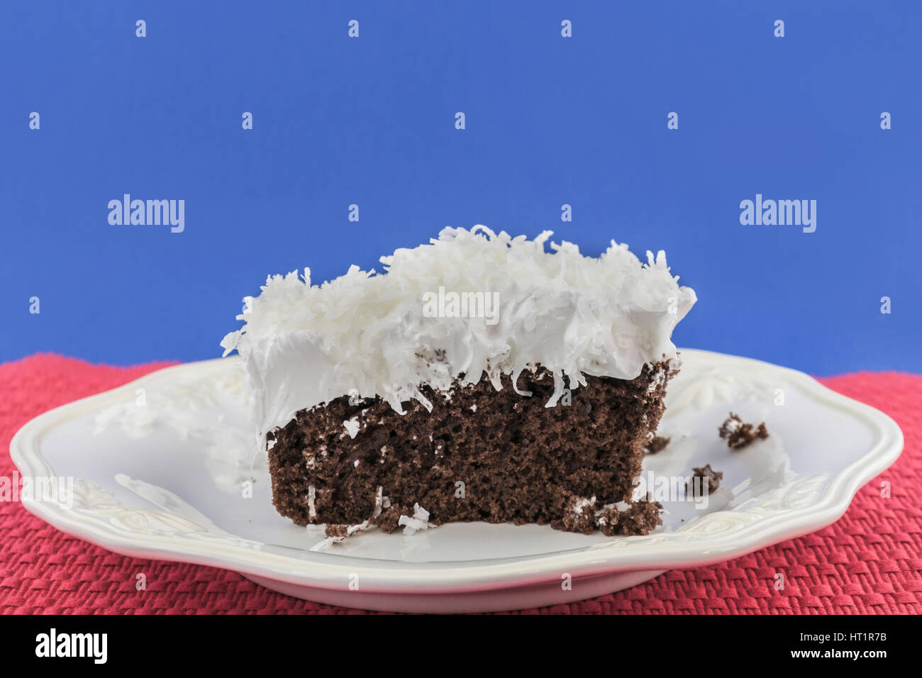 A piece of chocolate cake with fluffy white frosting topped with shredded coconut on a white serving plate. Oklahoma, - Stock Image