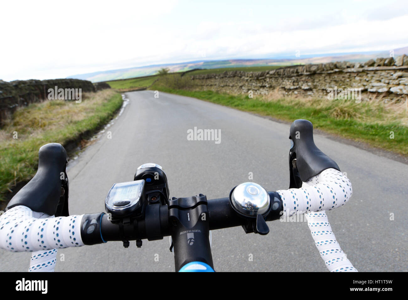 Cycling along a quite country lane low angle of the cyclist handlebars - Stock Image