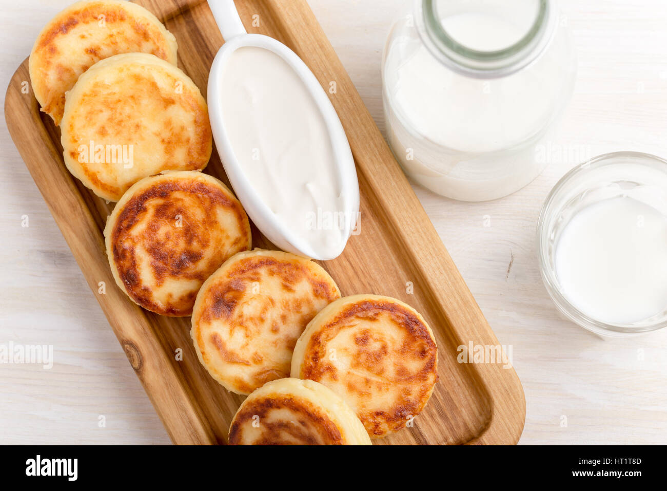 Homemade cottage cheese pancakes on white wooden table served with sour cream. Syrniki, traditional Ukrainian cuisine Stock Photo