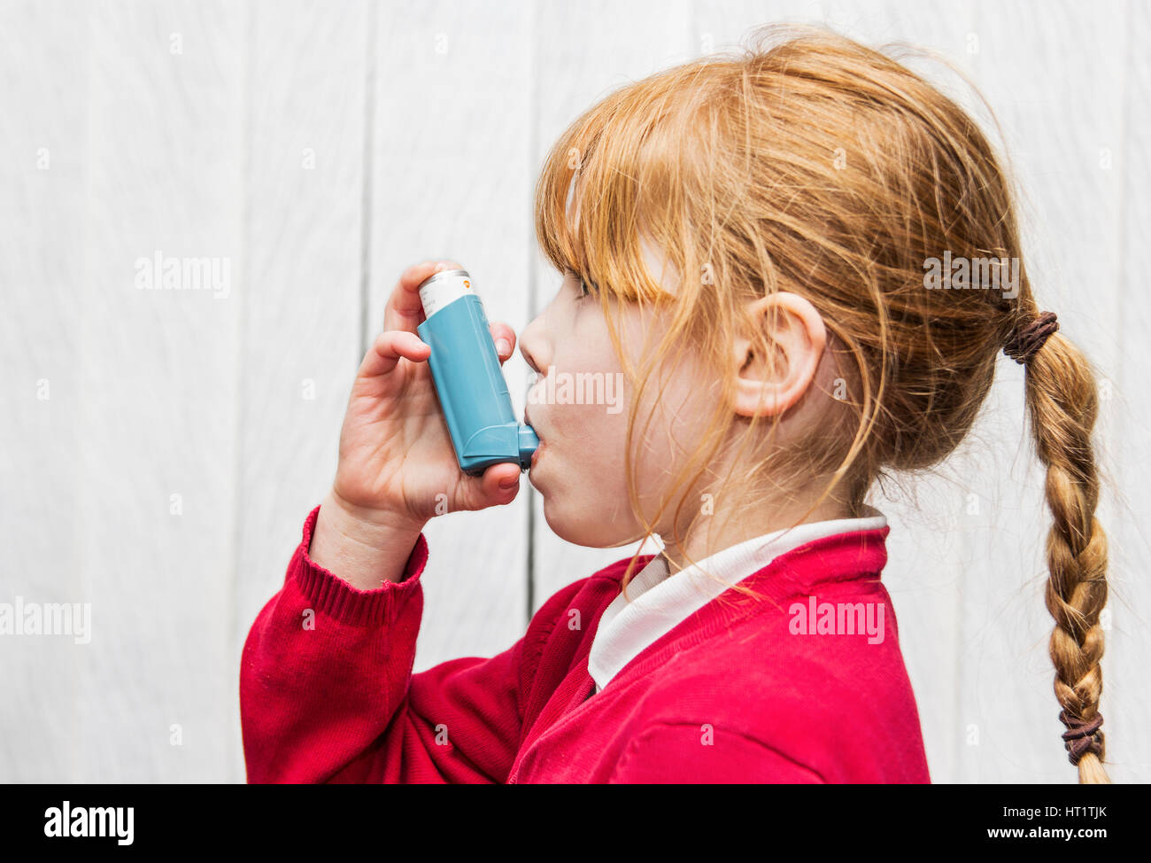 Ventolin asthma inhaler use by 7 year old Caucasian girl - Stock Image