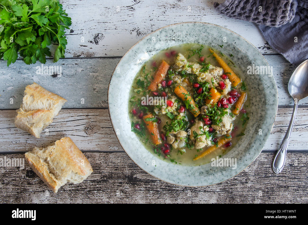 Carrot, parsnip and freekeh chicken soup with rustic bread - Stock Image