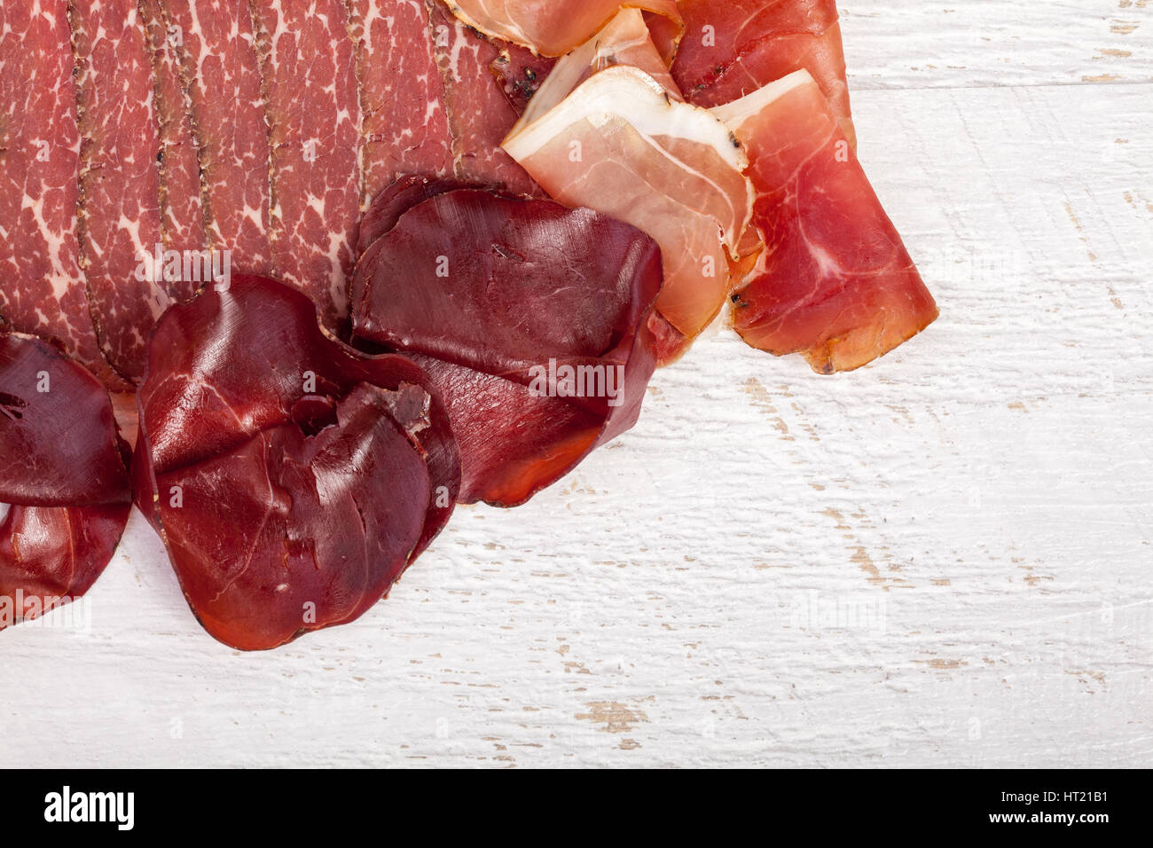 Different Type Of Delicious Ham On Wooden Background In Studio Photo