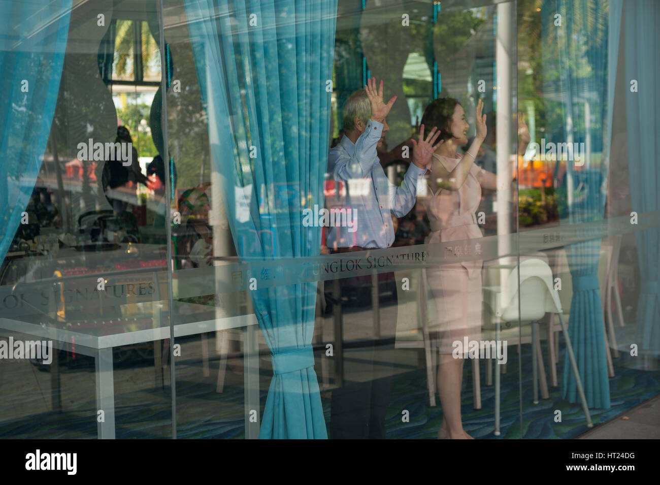 02.10.2016, Singapore, Republic of Singapore - People wave at children on the street from inside a restaurant at - Stock Image