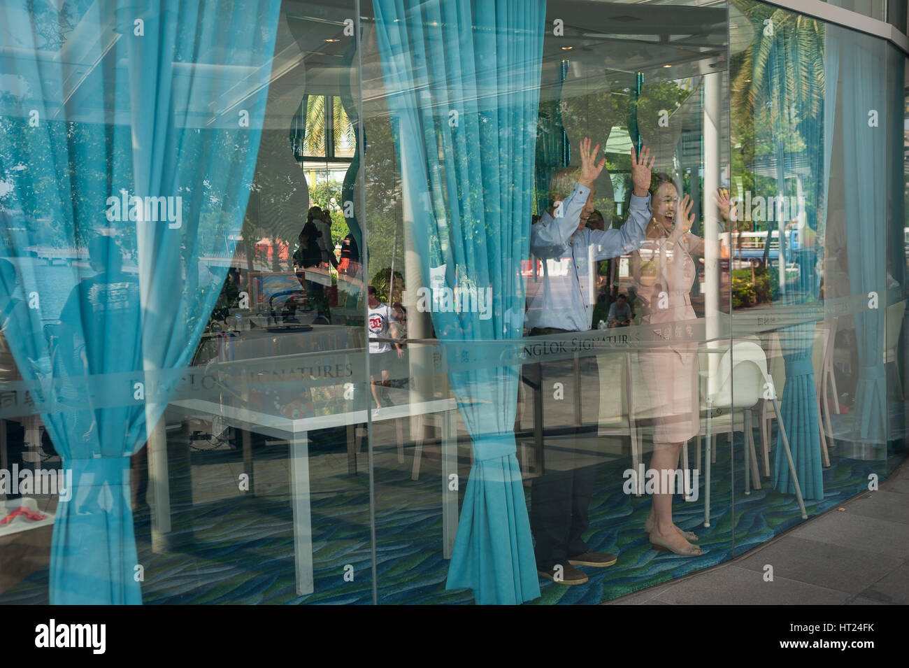 02.10.2016, Singapore, Republic of Singapore - People wave at children on the street from inside a restaurant at Stock Photo