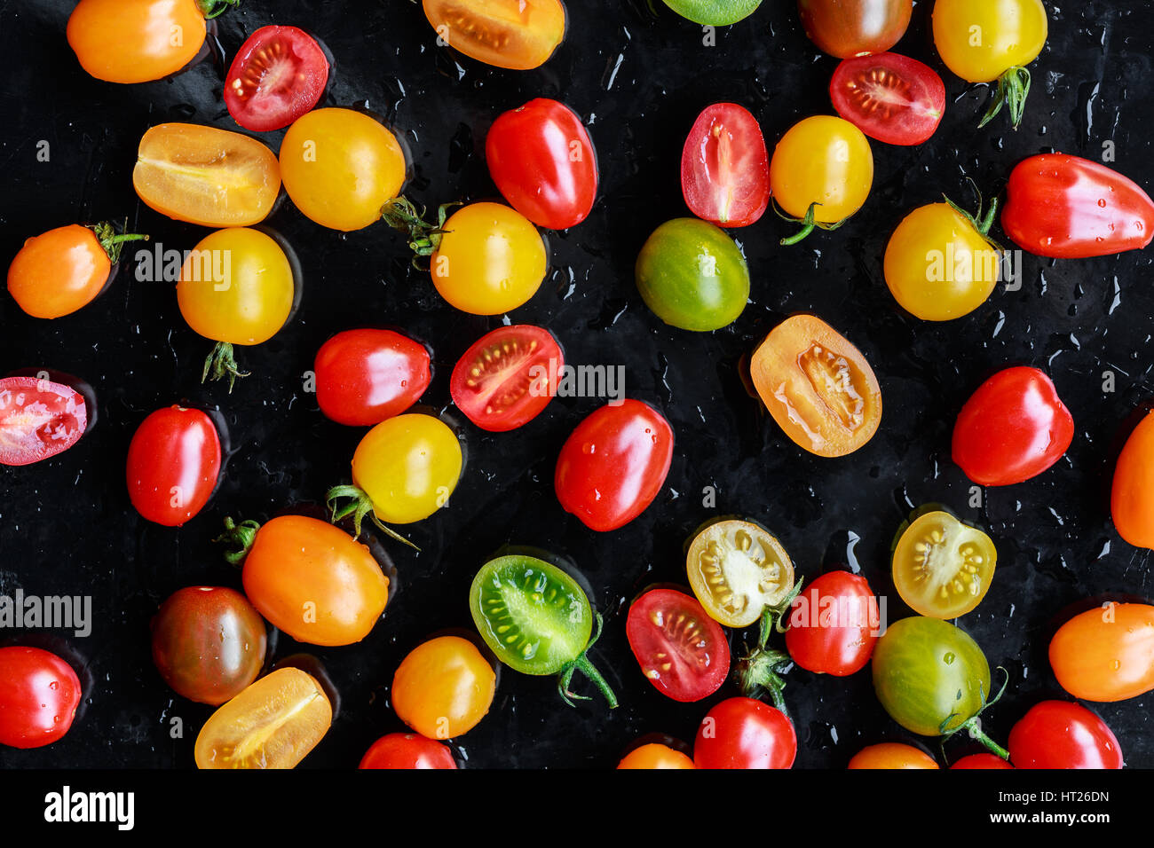 Multi-colored tomatoes on black background - Stock Image