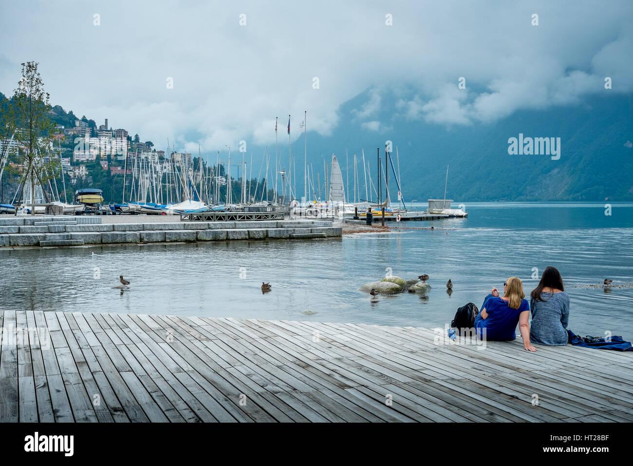Two girls enjoy the tranquil waters of Lake Lugano, Switzerland. Stock Photo