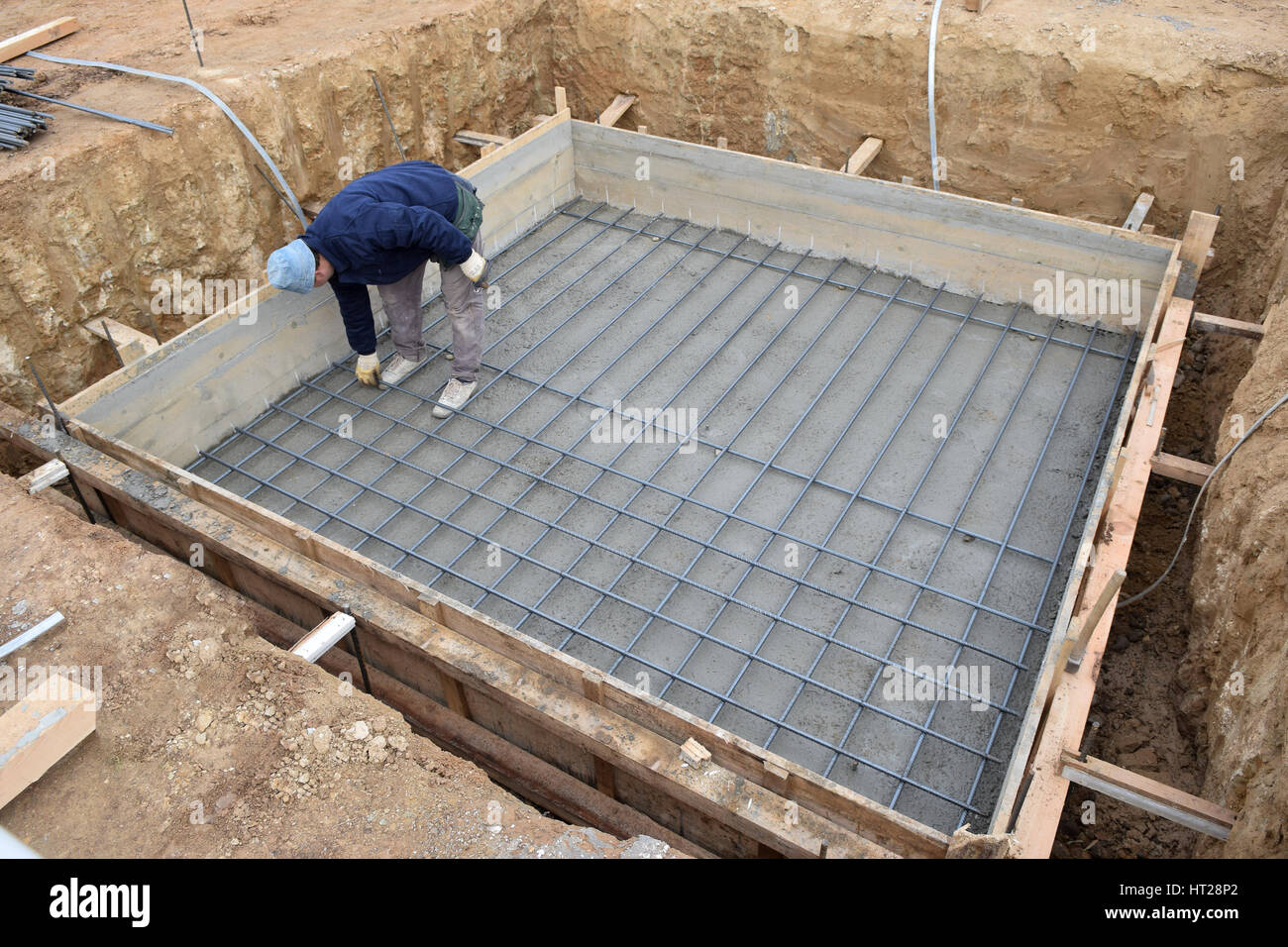 A big hole of pole in construction site building prepare for pouring cement.Worker controlled steel Stock Photo