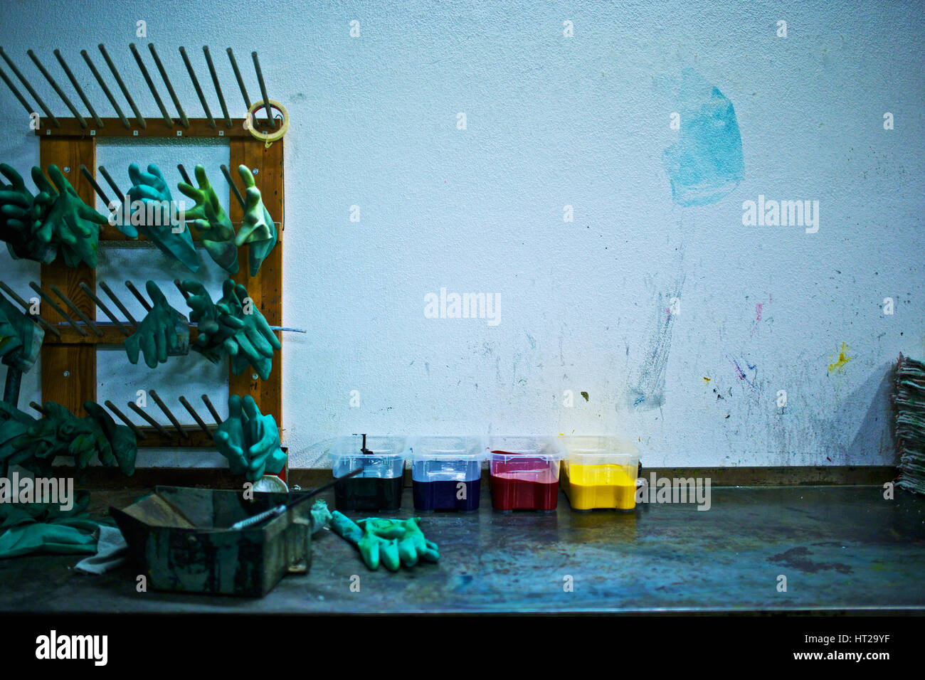 CMYK containers of paint and gloves inside a printing plant. - Stock Image