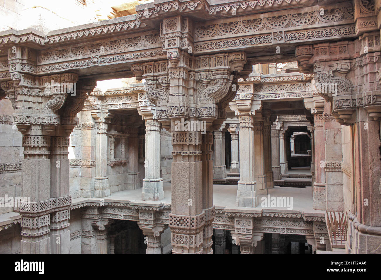 Upper storeys with intricate stone carvings on pillars, pilaster and entablature. Adalaj Stepwell, Ahmedabad, Gujarat, - Stock Image
