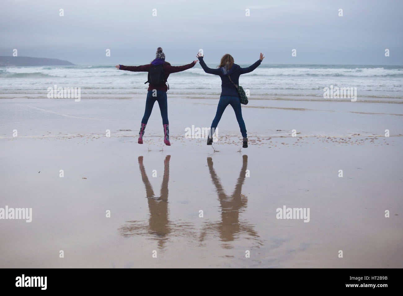 Two Girls Doing Star Jumps on Godrevy Beach, Cornwall UK - Stock Image