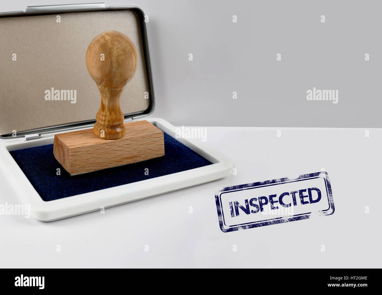 Wooden stamp on a desk INSPECTED - Stock Image