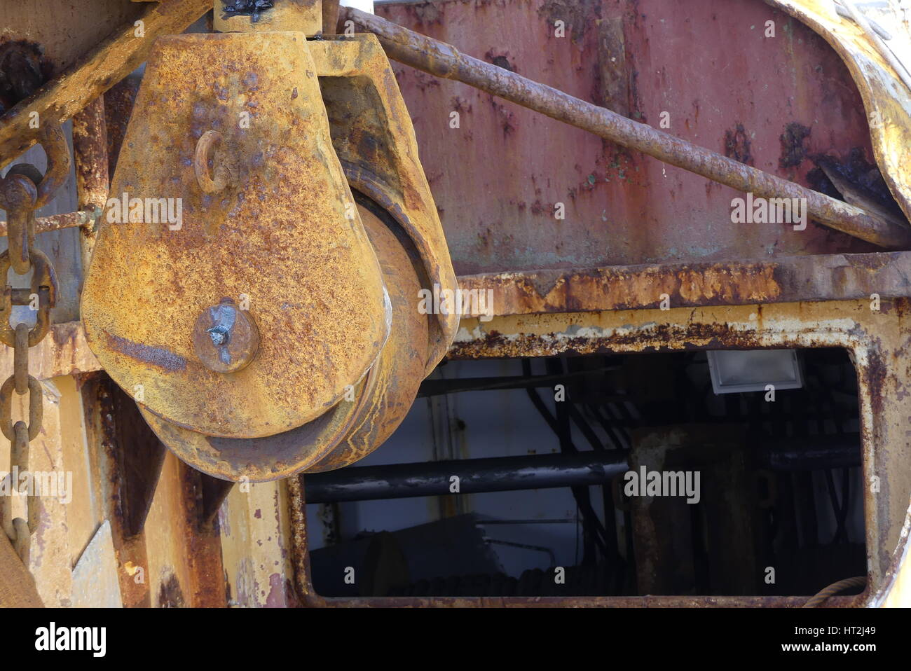 Closeup of  trawler cable warp pulley on the stern of a steel fishing boat with rust and corrosion by salt water - Stock Image