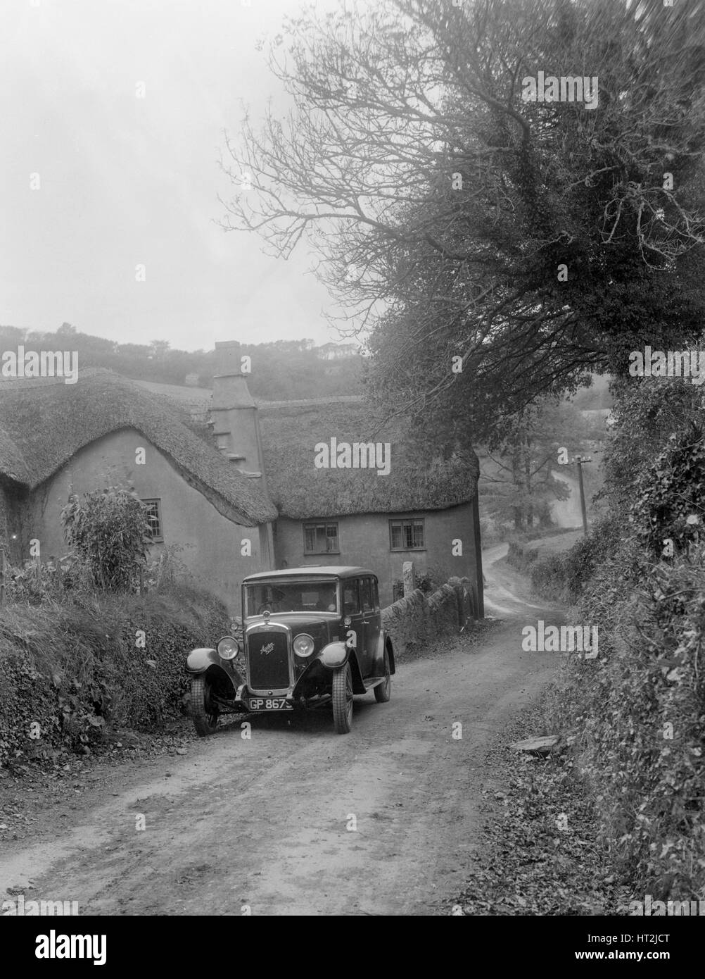 1931 Austin 16/6 on a road test, parked outside Parliament Cottage, Stoke Gabriel, Devon. Artist: Bill Brunell. - Stock Image