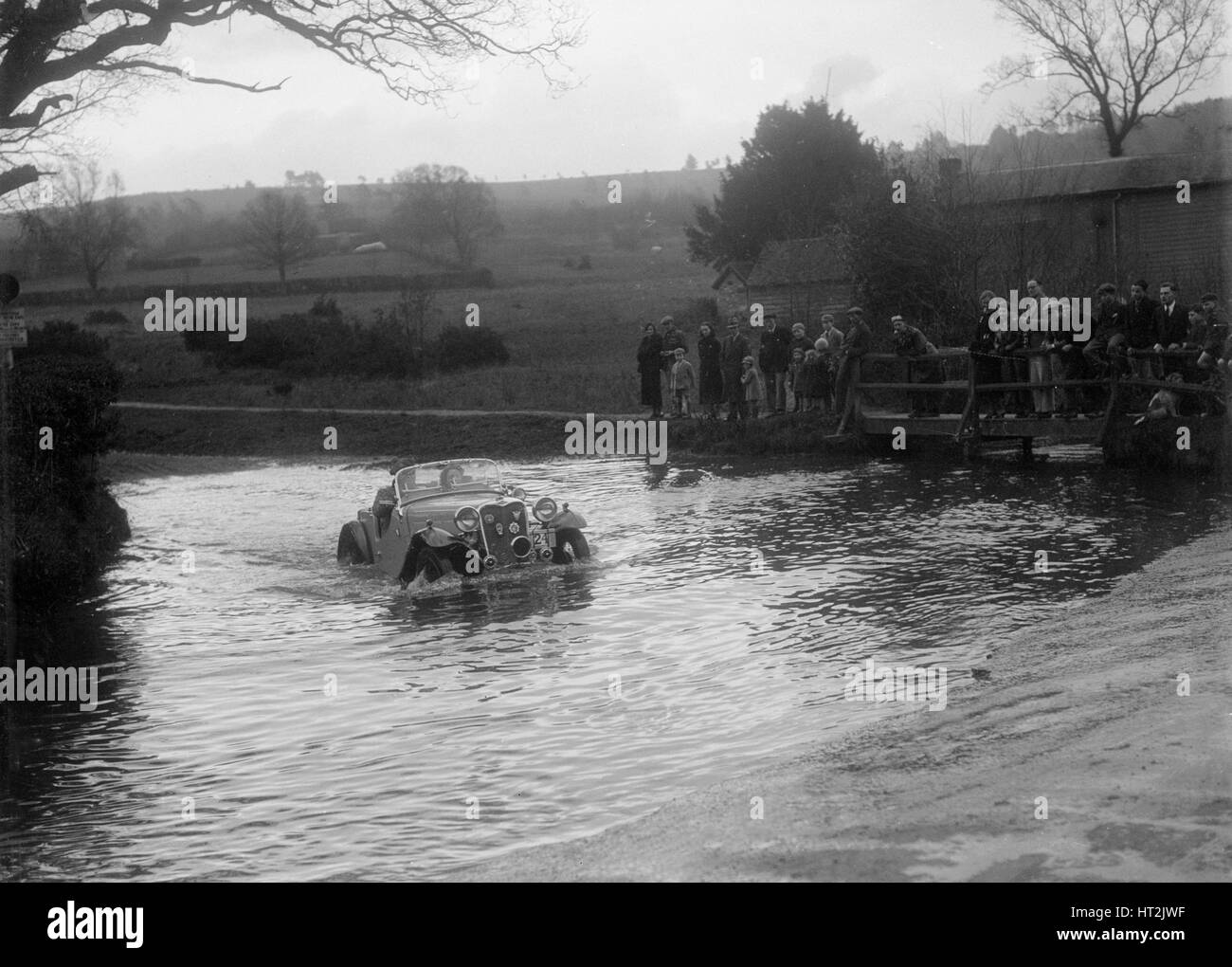 972 cc Singer Le Mans driving through a ford during a motoring trial, 1936. Artist: Bill Brunell. - Stock Image