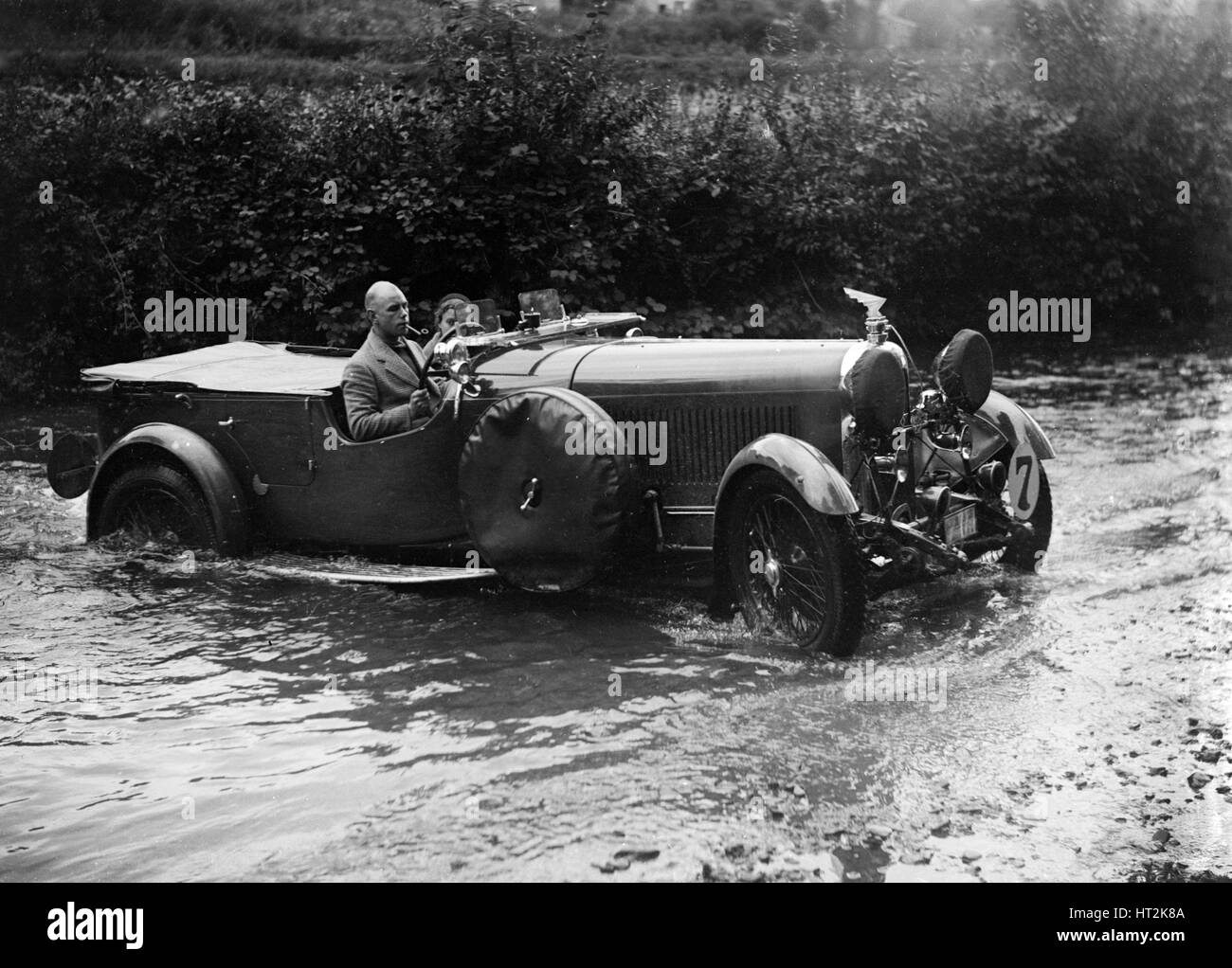 3-litre Lagonda of RD Tong fording the River Exe at Yealscombe, Devon, JCC Lynton Trial, 1932. Artist: Bill Brunell. - Stock Image