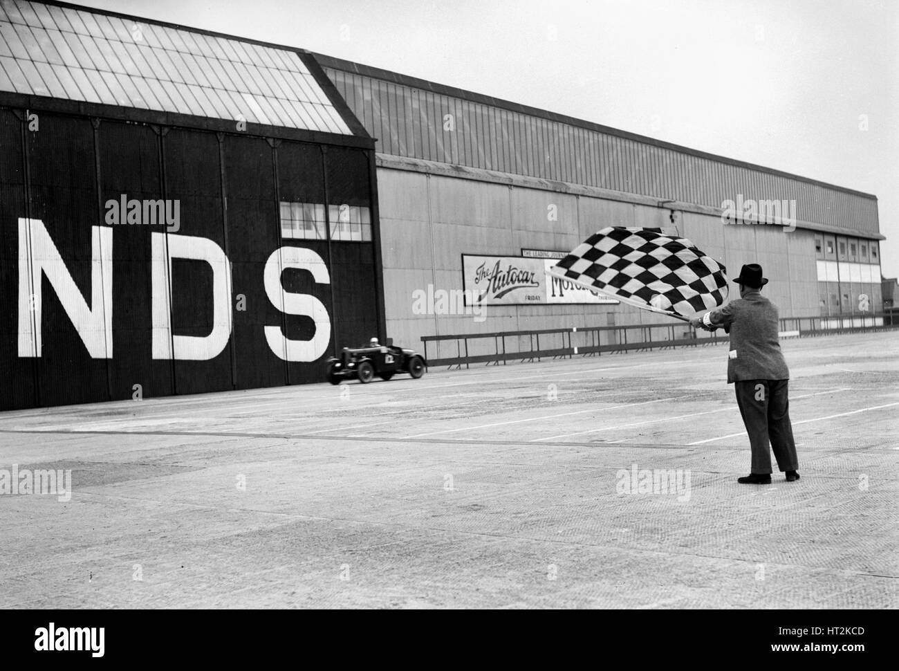 Waving the chequered flag at Brooklands, 1938 or 1939. Artist: Bill Brunell. - Stock Image