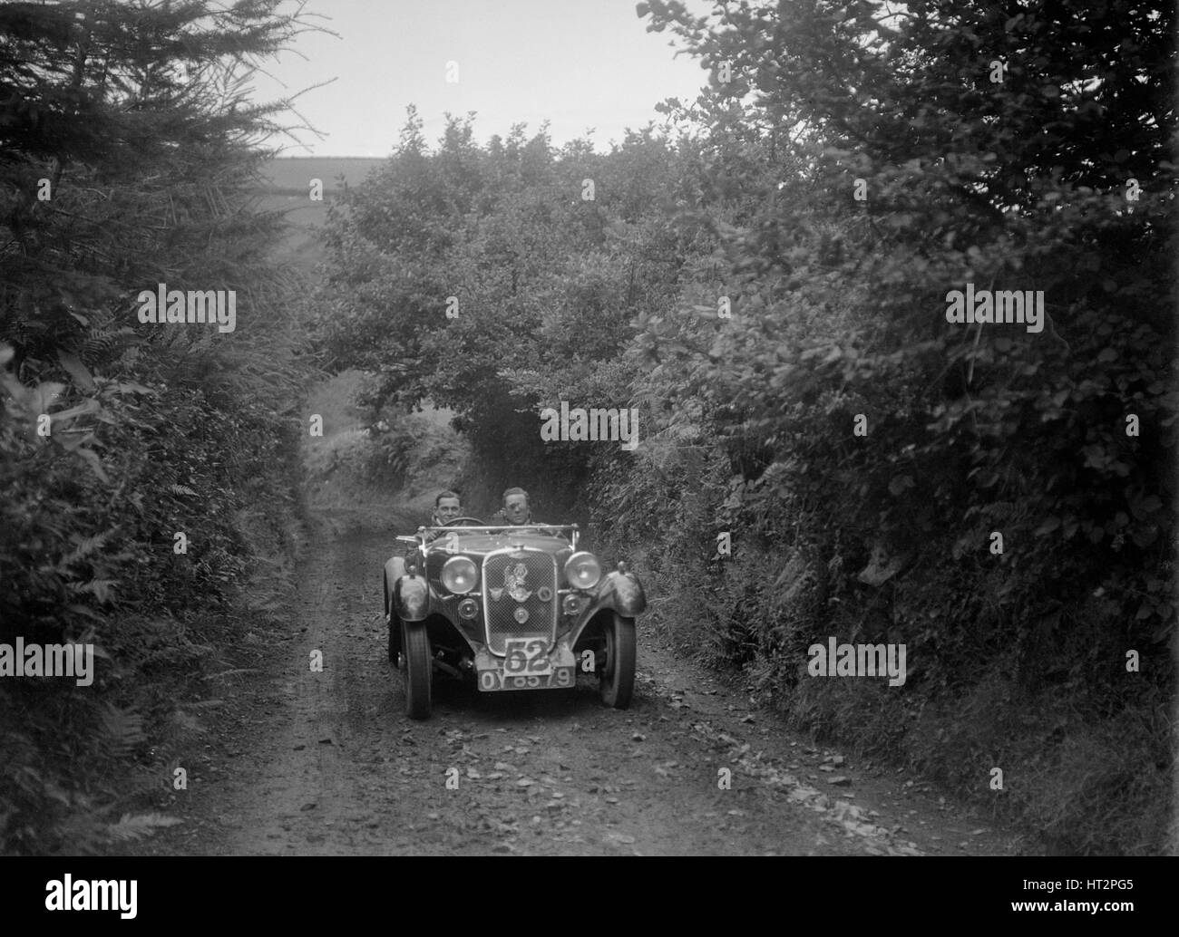 Singer open 2-seater competing in the Mid Surrey AC Barnstaple Trial, 1934. Artist: Bill Brunell. - Stock Image
