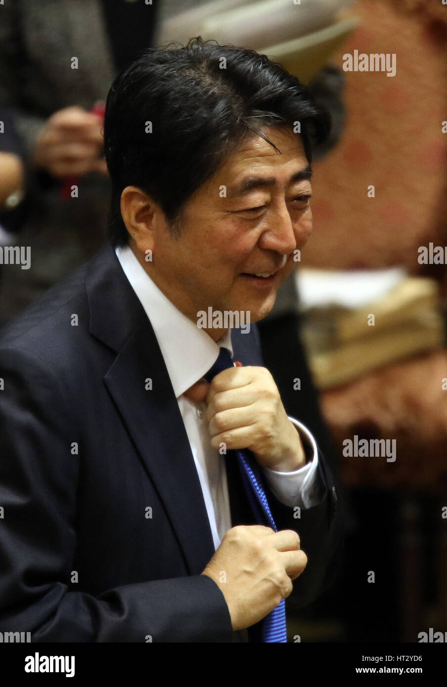 Tokyo, Japan. 6th Mar, 2017. Japanese Prime Minister Shinzo Abe adjusts his tie as he leaves the Upper House budget - Stock Image