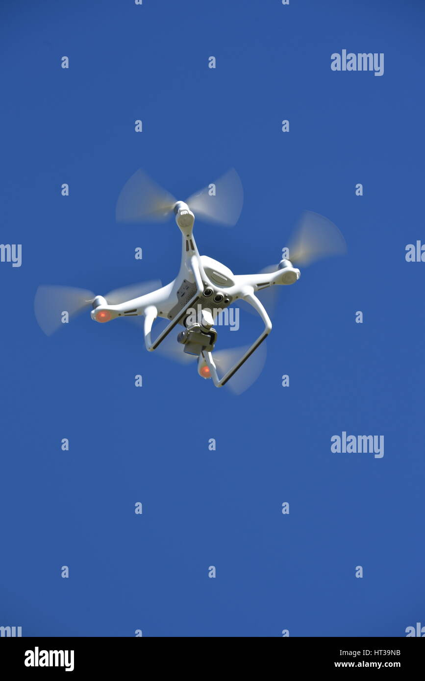 A view from below of a flying DJI Phantom 4 Drone  with a gimbal and camera attached.  Drone, photography, video, - Stock Image