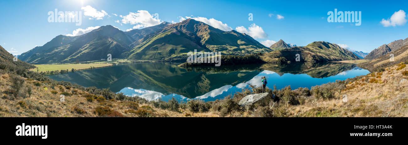 Hiker standing on rocks, mountains reflecting in lake, Moke Lake near Queenstown, Otago Region, Southland, New Zealand - Stock Image