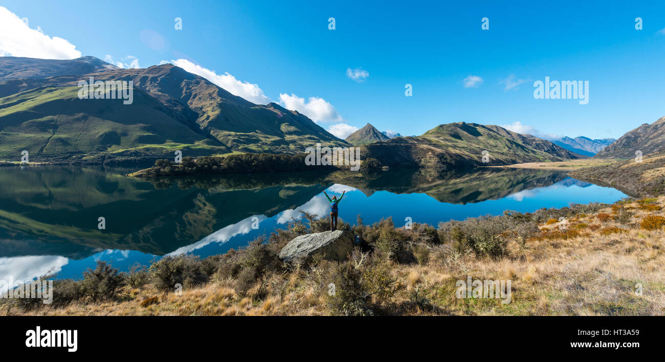 Hiker standing on rocks stretching out arms, mountains reflecting in lake, Moke Lake near Queenstown, Otago Region, - Stock Image