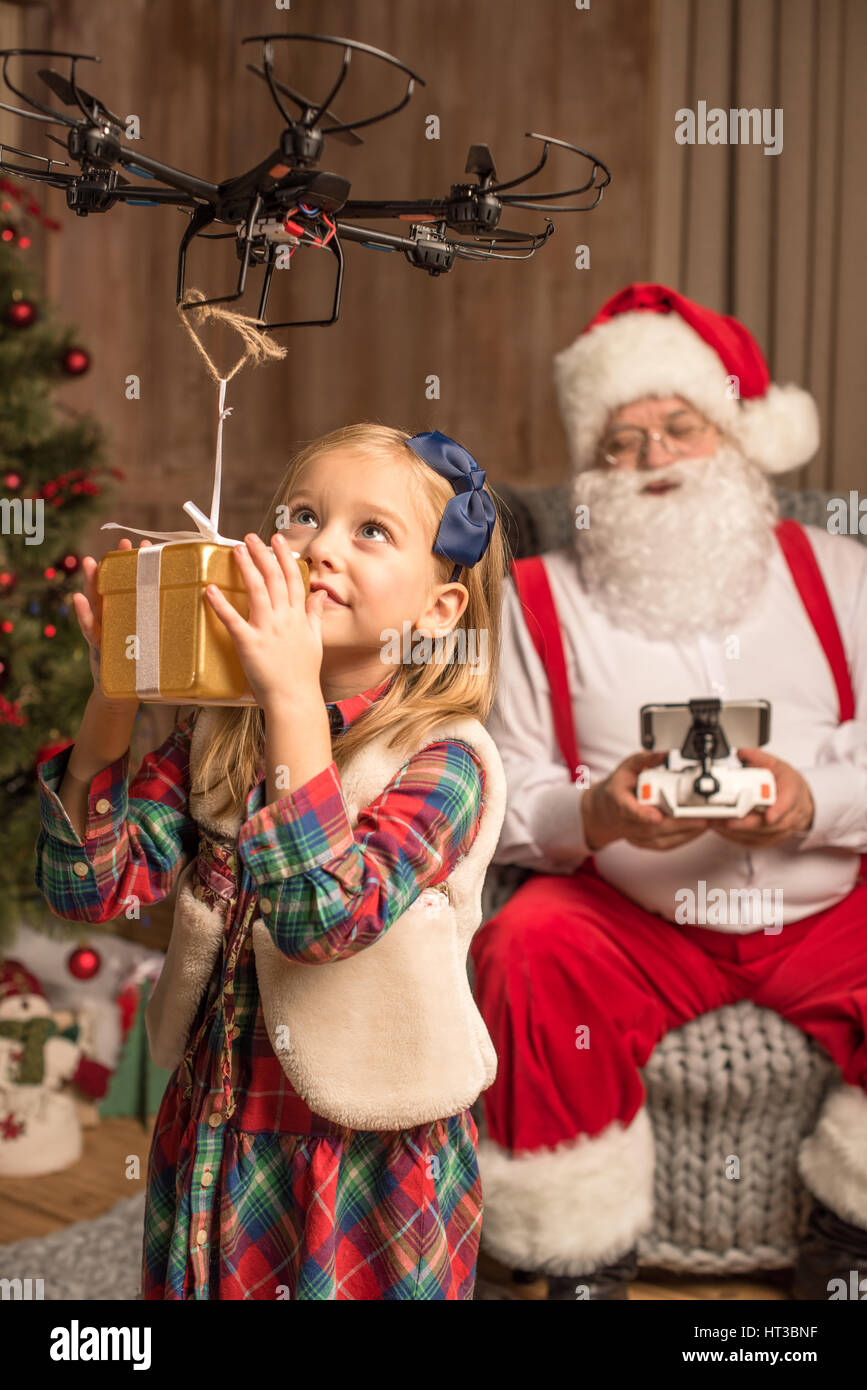 Santa with kid using hexacopter drone  - Stock Image