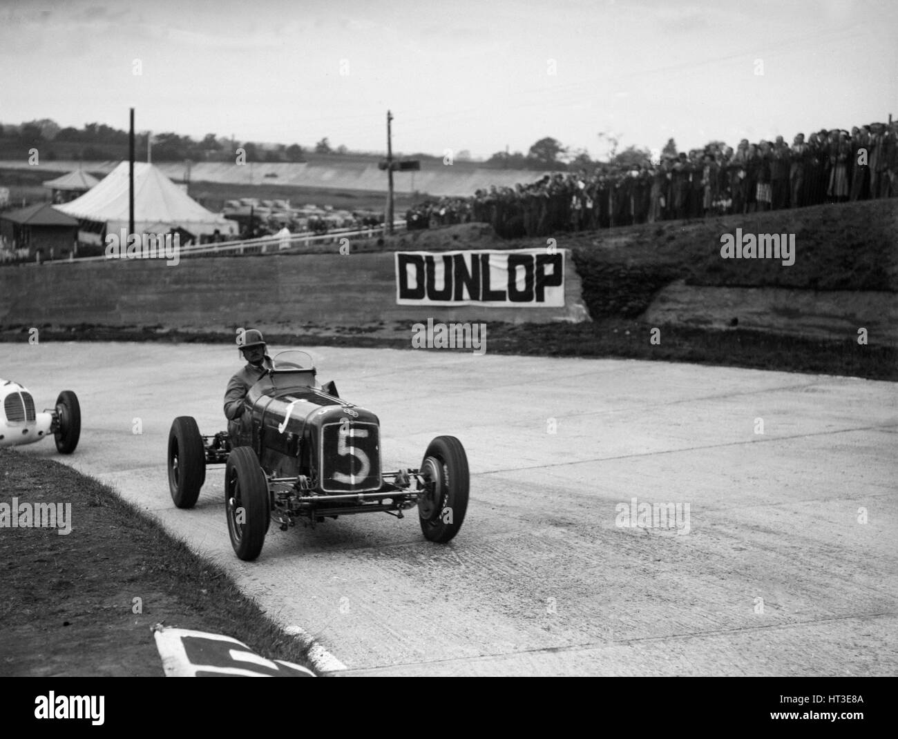 ERA and Maserati taking a corner in a race at Brooklands. Artist: Bill Brunell. - Stock Image