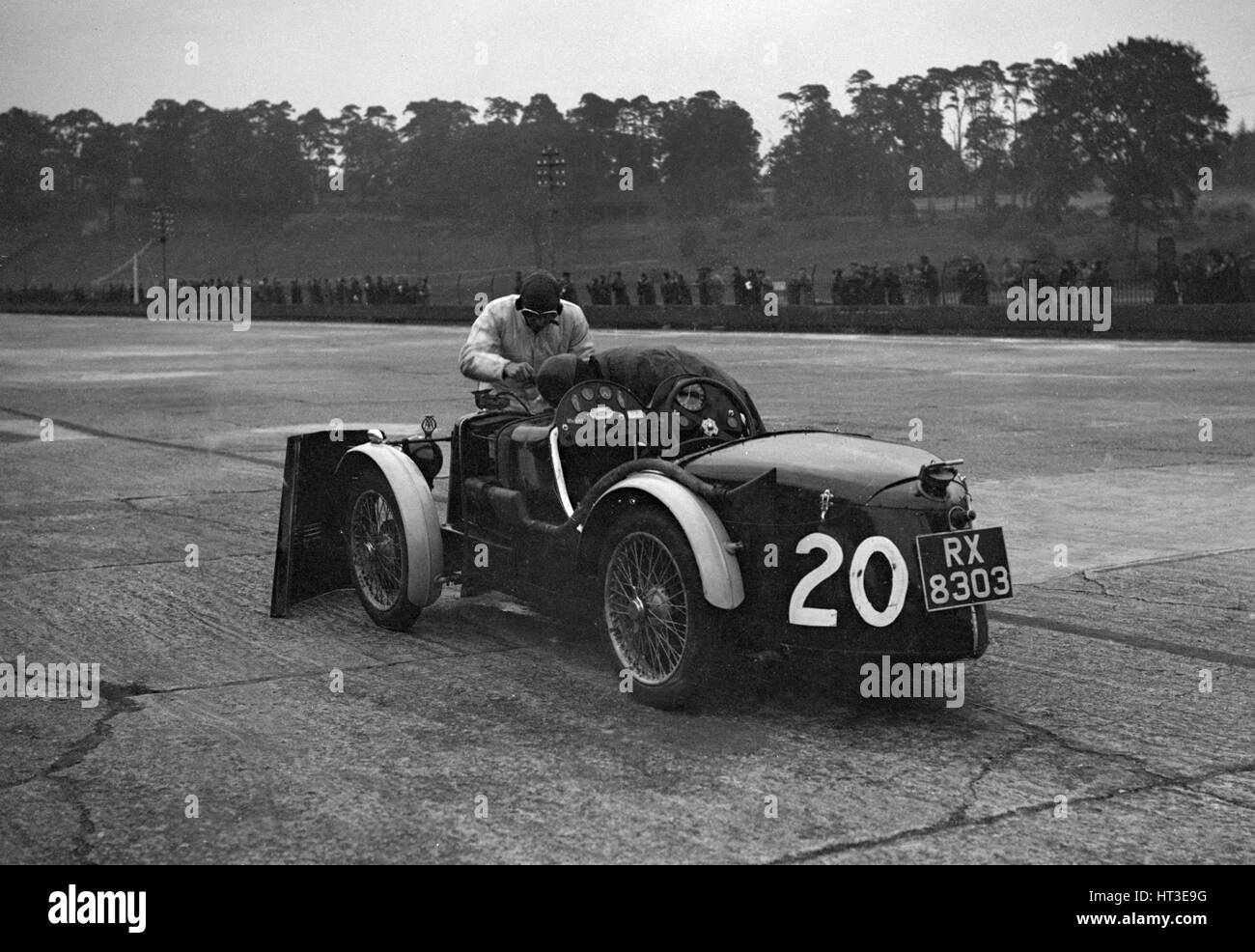 Mechanic making adjustments to a MG C type, Brooklands. Artist: Bill Brunell. - Stock Image