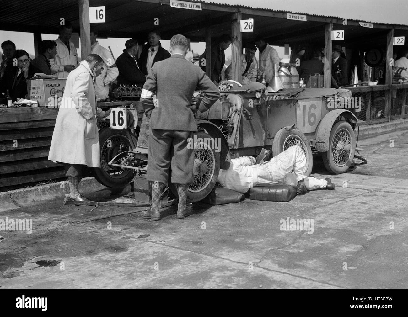Mechanic working on a Lea Francis J type at the JCC Double Twelve race, Brooklands, May 1931. Artist: Bill Brunell. - Stock Image