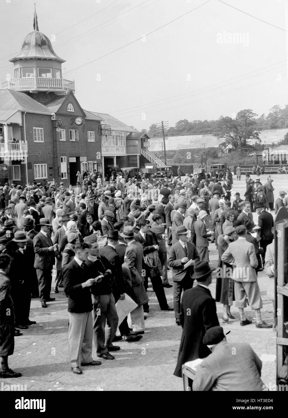 People attending a motor racing event at Brooklands. Artist: Bill Brunell. - Stock Image