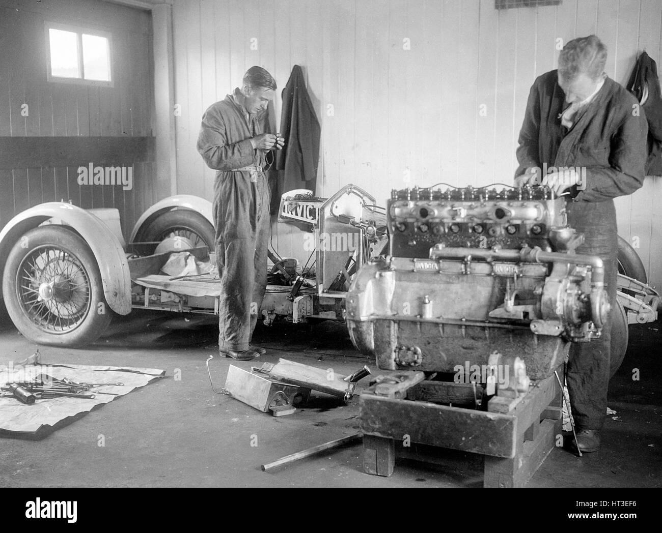 Mechanics working on Raymond Mays' 4500 cc Invicta car. Artist: Bill Brunell. - Stock Image