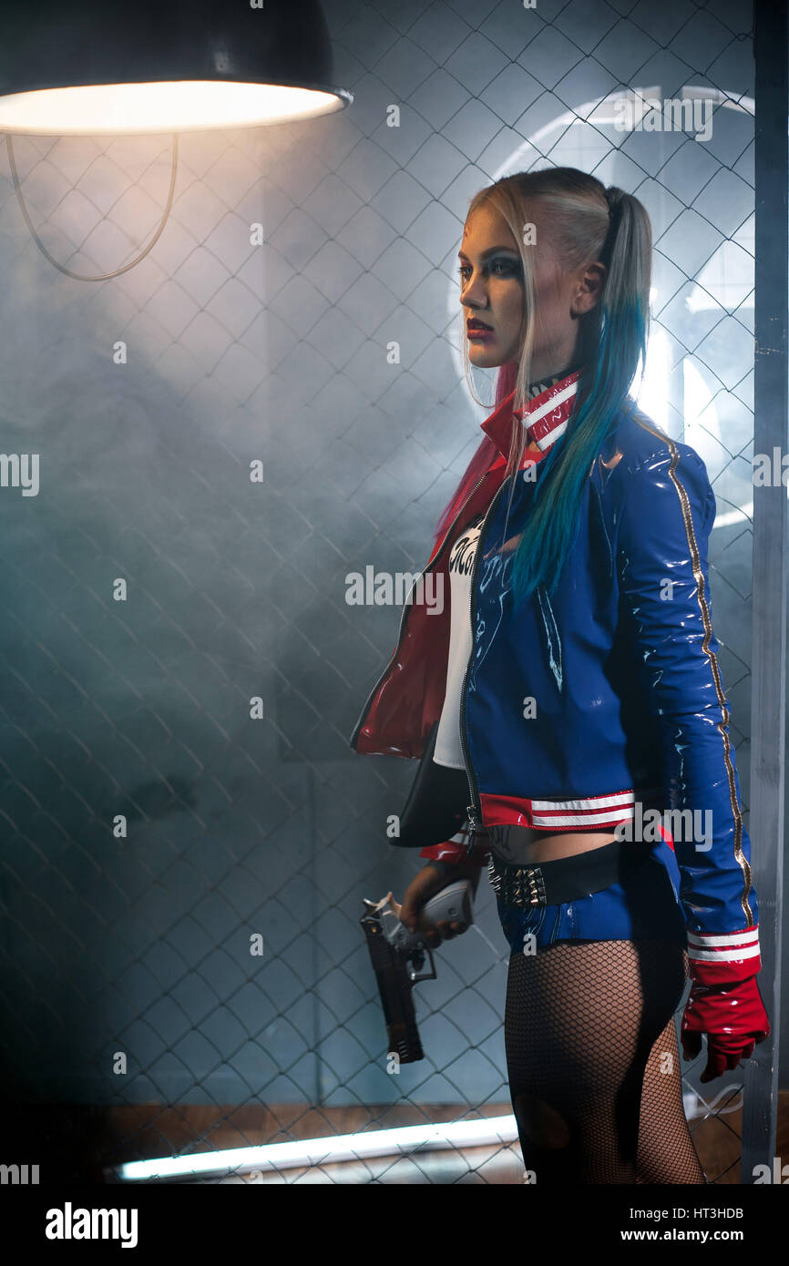 Girl in costume Harley Quinn with gun. Cosplay. She stands near grid under the lamp. Cosplay. - Stock Image