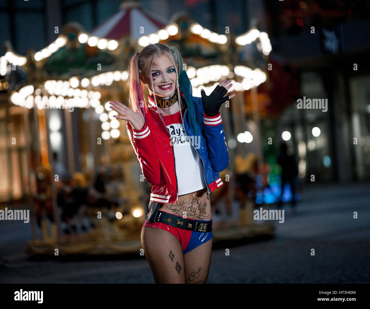Smiling girl in costume Harley Quinn on background of night city lights. Cosplay - Stock Image