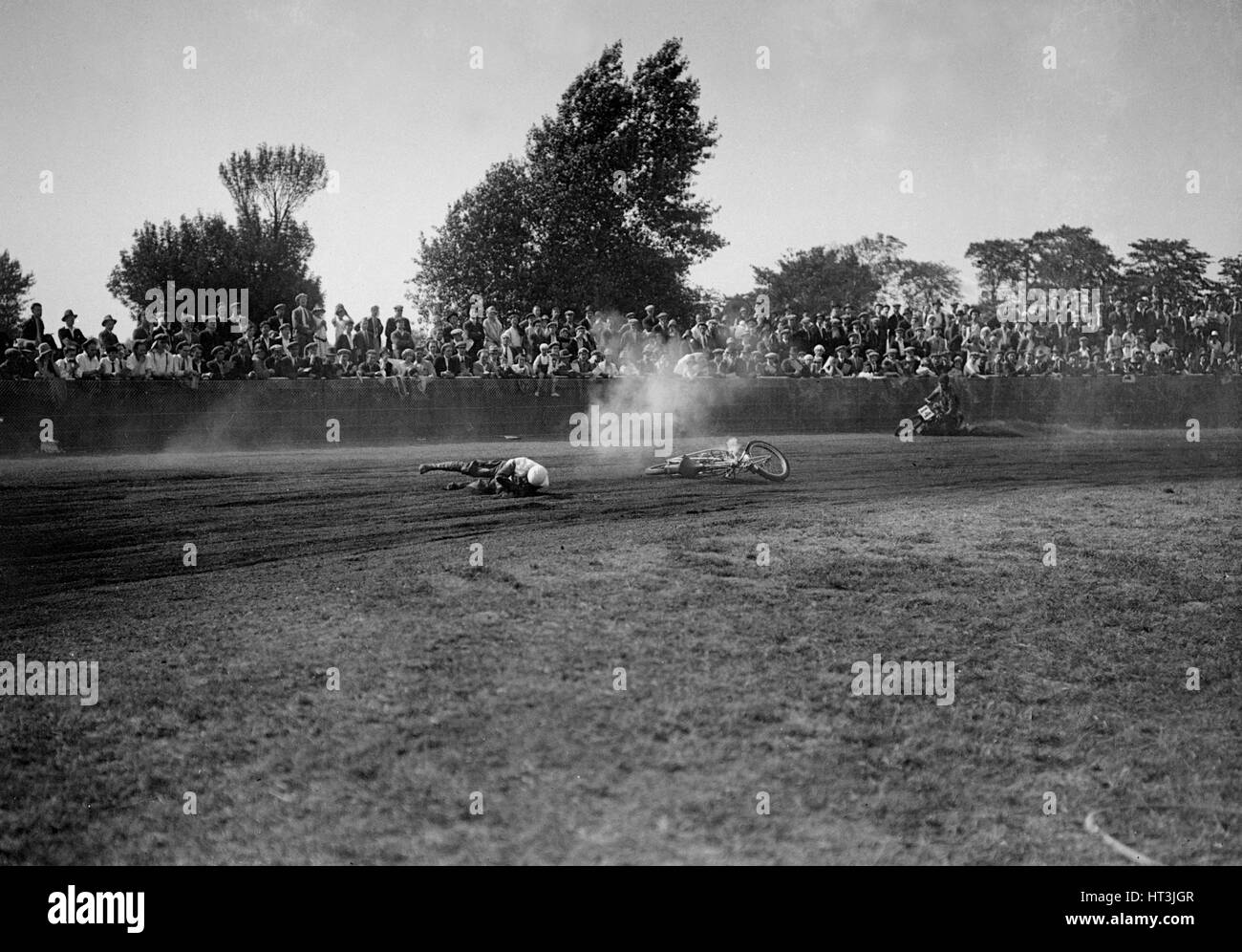 Fallen rider in a speedway race at Lea Bridge Stadium, Leyton, London, 1928.   Artist: Bill Brunell. - Stock Image