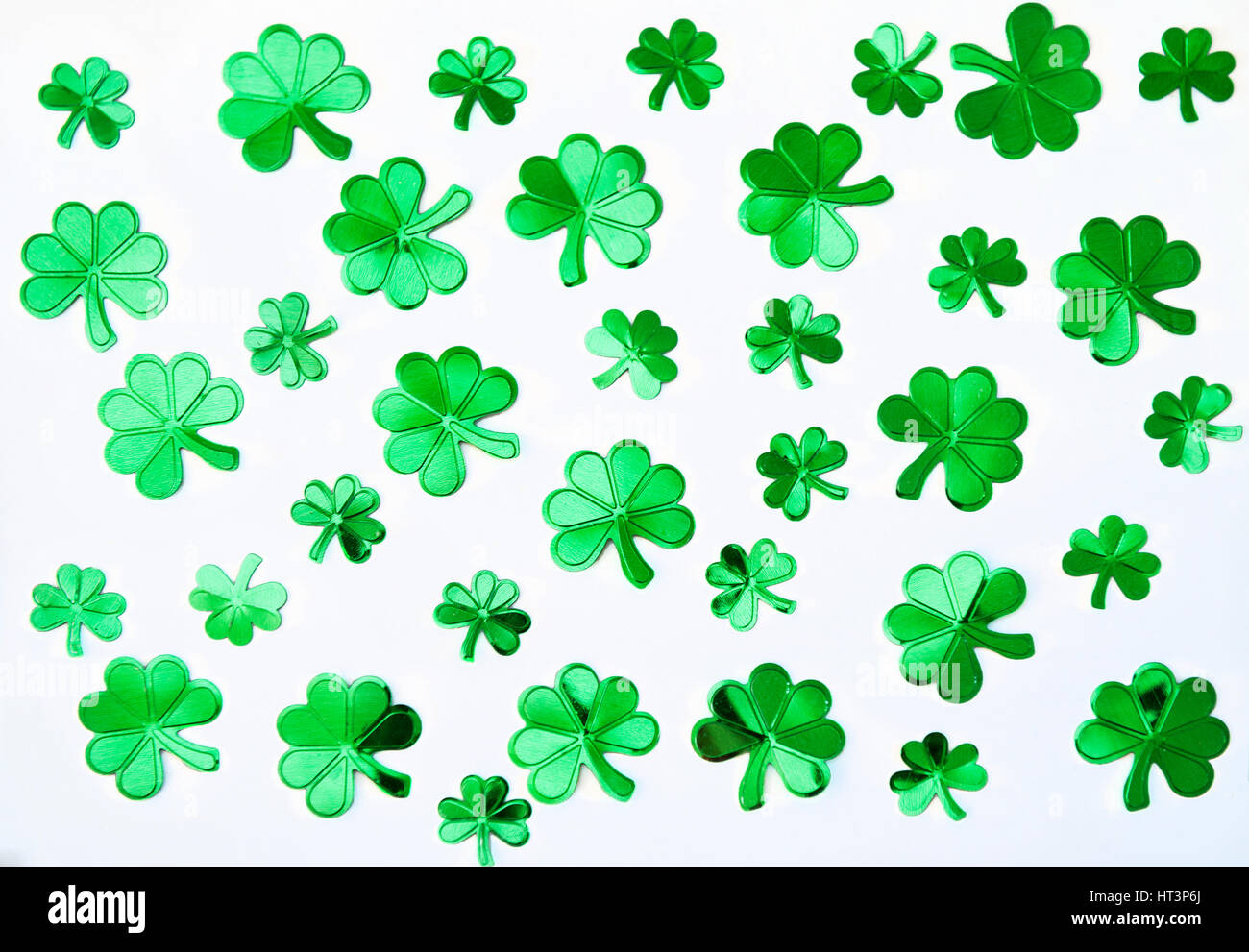 An abstract of green confetti shamrocks in a random pattern against a white background - Stock Image